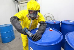worker in protection clothing filling a large drum with a hazardous substance