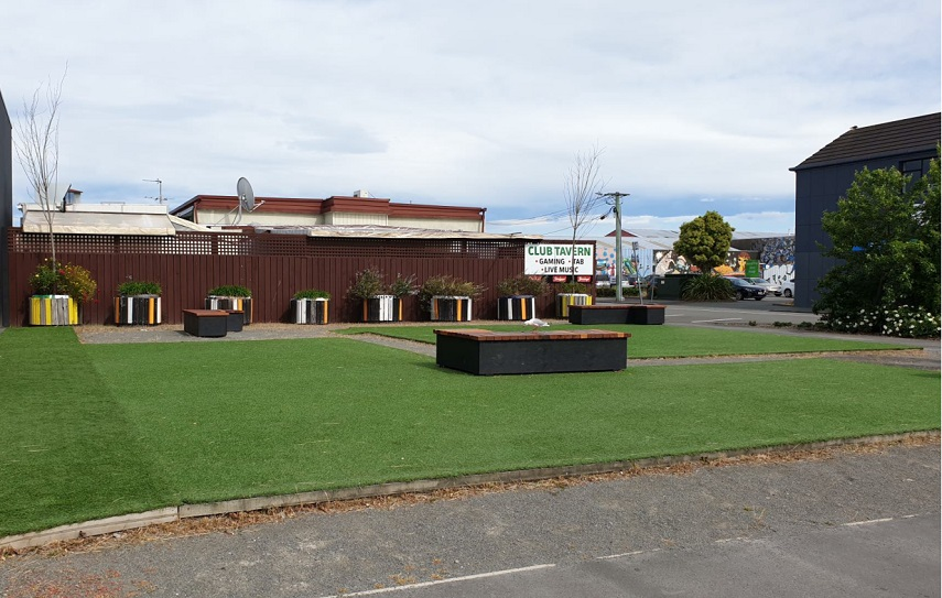 A pocket park featuring fake turf, benches and planters.