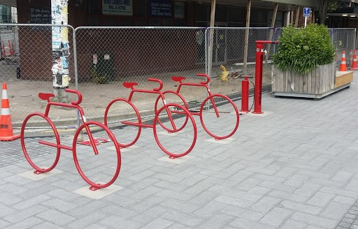 Three red bike stands and standing pump station
