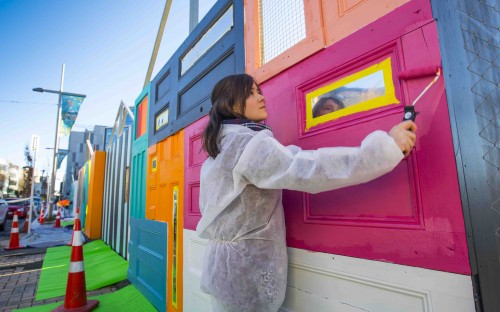 A young woman paints a hoarding constructed of doors.