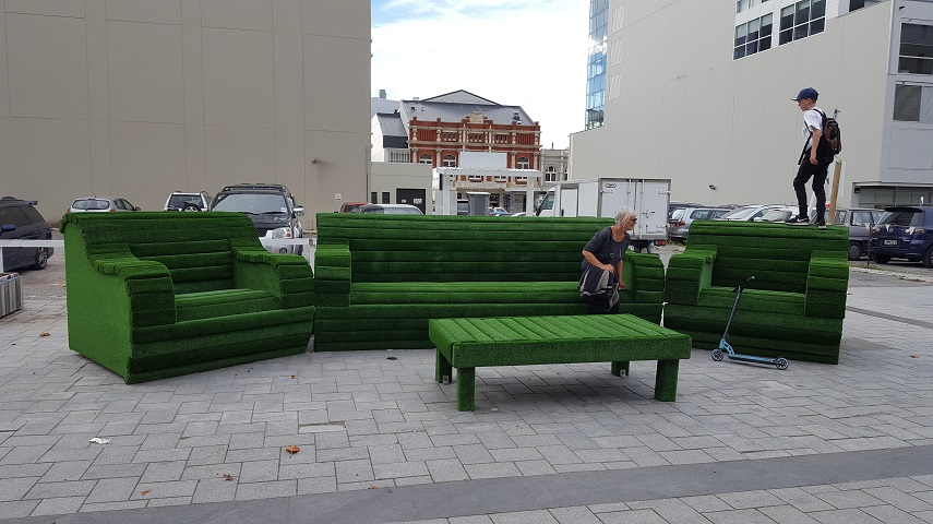 Two people sit on oversize green furniture