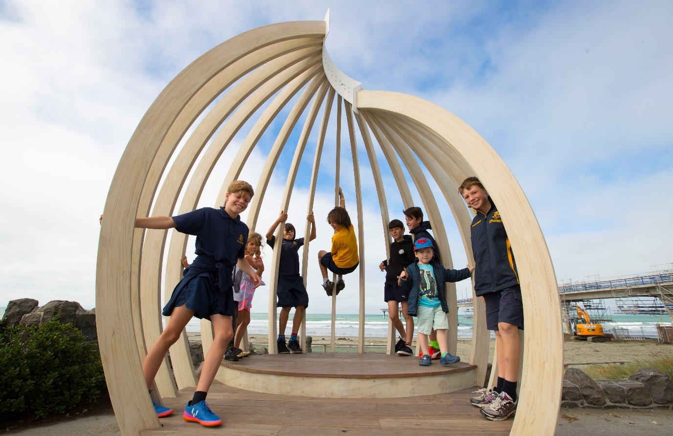 Children pose inside a shell shaped wooden structure