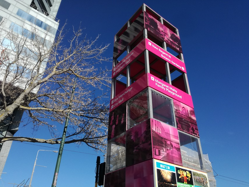 A tall pink tower displays directions to attractions
