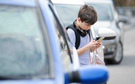 A child walks distractedly through traffic while playing on his phone.