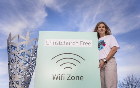 Teresa McCallum with the Christchurch Free wifi zone sign.