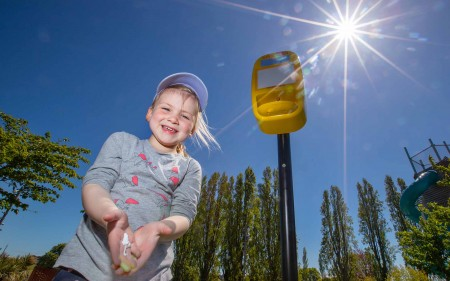 A young girl gets some free sunscreen at the Margaret Mahy playground.