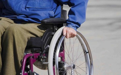 A man pushes himself in a wheelchair.