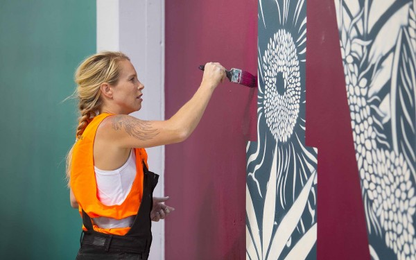 Artist Hayley King, aka Flox, painting the mural in Plymouth Lane.