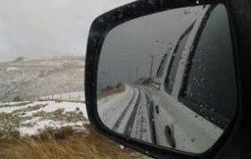 View in a car's side mirror of a snow covered landscape and road.