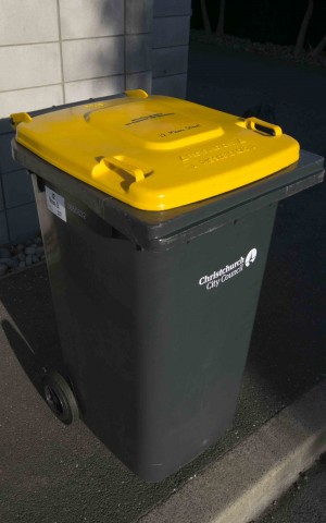 A yellow wheelie bin.
